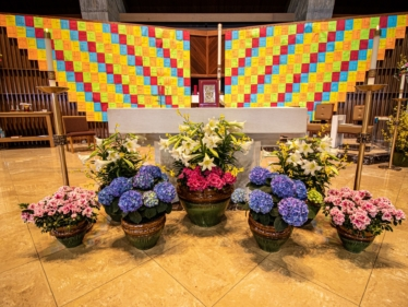 Colored pages bearing names of parishioners adorn the sanctuary at Saint Jude Church while we are unable to gather for Mass.